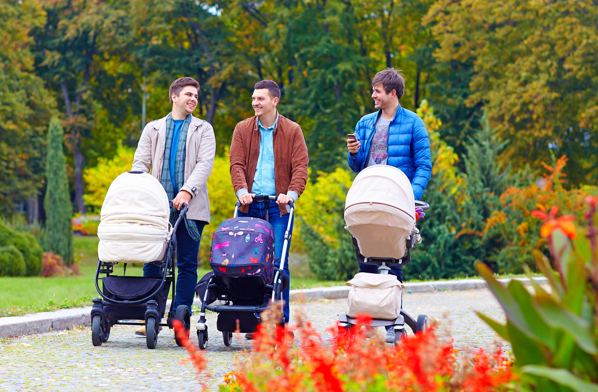 three friends, fathers walking with buggies in city park