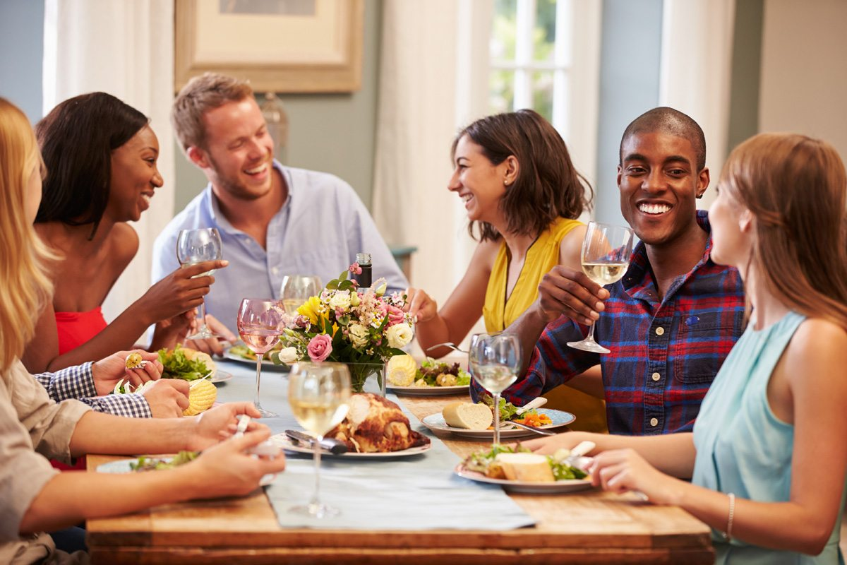 Friends At Home Sitting Around Table For Dinner Party